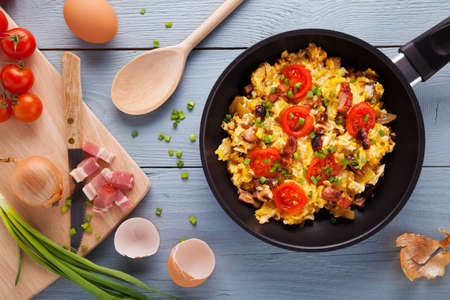 breakfast plate: Scrambled eggs in a pan with bacon, onion and tomatoes sprinkled with chives, prepared from small farm eggs.