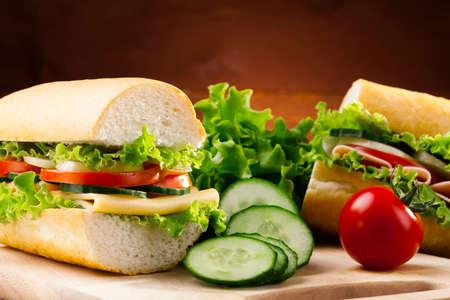 jamon y queso: gran s�ndwich con jam�n, queso y verduras en woodboard Foto de archivo