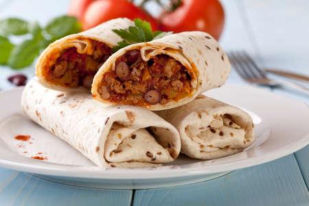 burrito wraps met vlees bonen en groenten op blauw houten bord