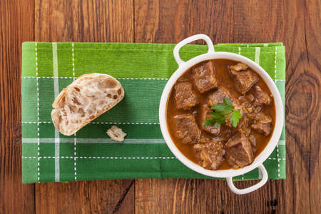 Beef stew served with bread in a plate on a wooden background Stok Fotoğraf - 37876591