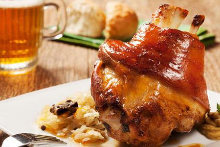 Geroosterde knokkel van varkensvlees met gekookte kool, brood, mierikswortel en mosterd, geserveerd met een beker koud bier