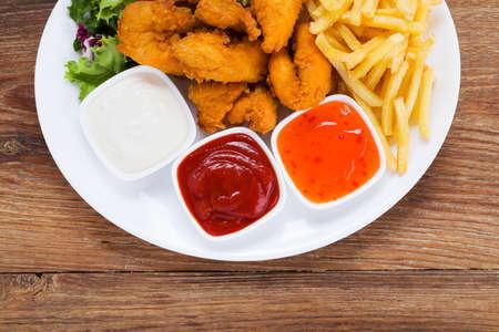 nuggets de pollo: Nuggets y patatas fritas en un plato servido con salsa y ensaladas en una tabla de madera Foto de archivo