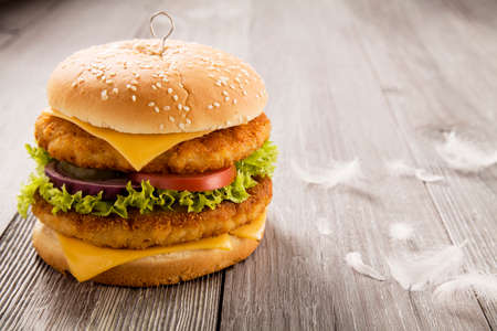 burger background: Home made chicken burger with cheese, lettuce, tomato and onion on wooden board Stock Photo