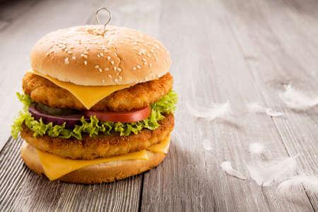 Zelfgemaakte kip hamburger met kaas, sla, tomaat en ui op een houten plank