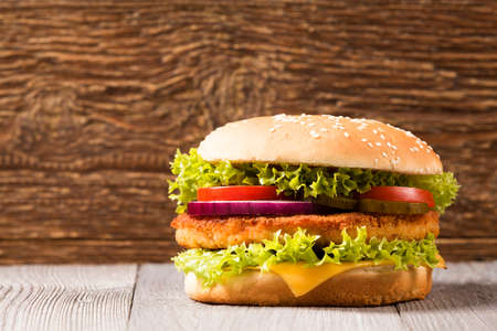 Home made chicken burger with cheese, lettuce, tomato and onion on wooden board Stock Photo