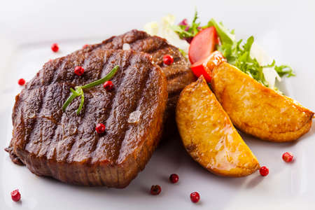 Grilled beef steak with baked potatoes and vegetables on plate Stok Fotoğraf