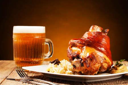 Gebratene Schweinshaxe mit gekochtem Kohl, Brot, Meerrettich und Senf, serviert mit einer Tasse kaltes Bier Standard-Bild