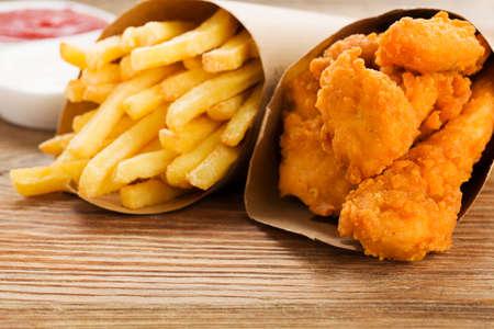 fish and chips: Nuggets y patatas fritas que se sirven en una bolsa de papel con un chapuzón en una tabla de madera