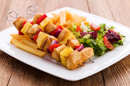 Grilled chicken skewers with pineapple, peppers and onions served with french fries and vegetable salad