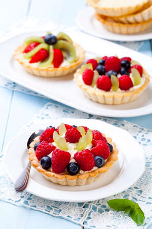 tartlet: Delicious tartlets with fruit and cream mascaropne on plate Stock Photo