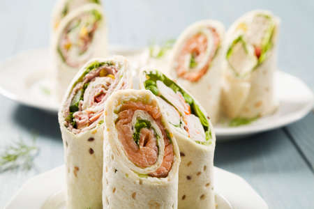 fresh fish: Mix of wraps with ham, chicken, salmon and crab served on a plate