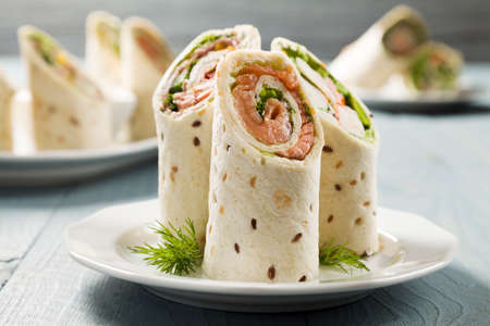 Mix of wraps with ham, chicken, salmon and crab served on a plate