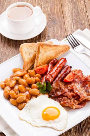 comida inglesa: Ingl�s desayuno con bacon, salchichas, huevo frito, frijoles horneados y t� o jugo de naranja Foto de archivo