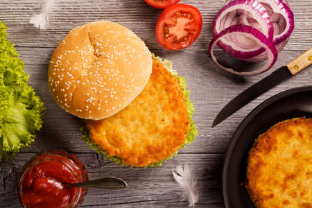 chicken burger: Home made chicken burger with lettuce, tomato and onion on wooden board Stock Photo