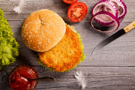 Home made chicken burger with lettuce, tomato and onion on wooden board Stok Fotoğraf
