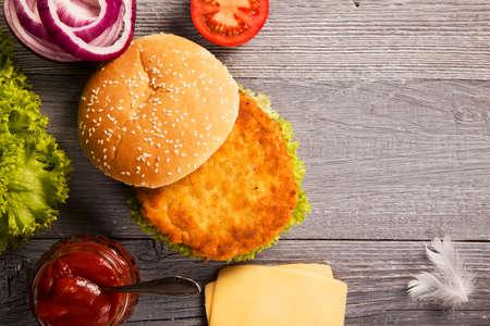 Home made hamburger di pollo con formaggio, lattuga, pomodoro e cipolla su tavola di legno Archivio Fotografico - 39142854