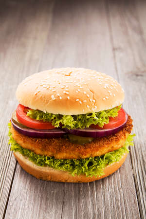 Home made chicken burger with lettuce, tomato and onion on wooden board Stock Photo