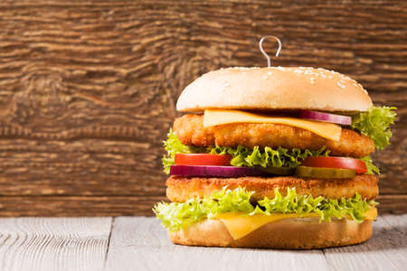 chicken burger: Home made chicken burger with cheese, lettuce, tomato and onion on wooden board Stock Photo