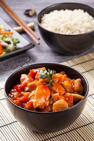 Chinese kip zoetzure saus, geserveerd met rijst en groenten op woodboard