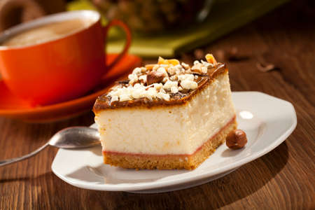 cheesecake with nuts on plate, dark background, selective focus photo