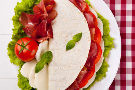 Italian Piadina Romagnola with mozzarella, ham and vegetables on white woodboard photo
