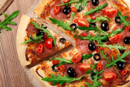 peperoni: Pizza peperoni on plate with black olives, rocket and mozzarella cheese Stock Photo