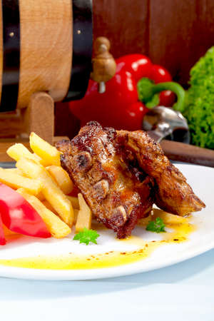 Grilled ribs on plate, served with fries photo