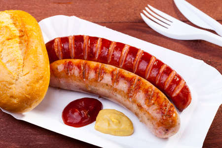 Roasted sausage with bread served on a paper tray - wood board