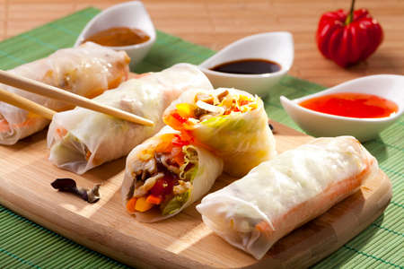 Portion of spring rolls on a bamboo board with dipping sauce