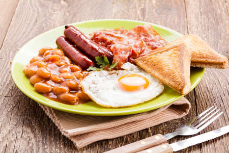 bacon baked beans: English breakfast with bacon, sausage, fried egg, baked beans and tea or orange juice