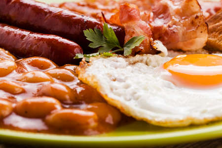 English breakfast with bacon, sausage, fried egg, baked beans and tea or orange juice Stok Fotoğraf - 41142323