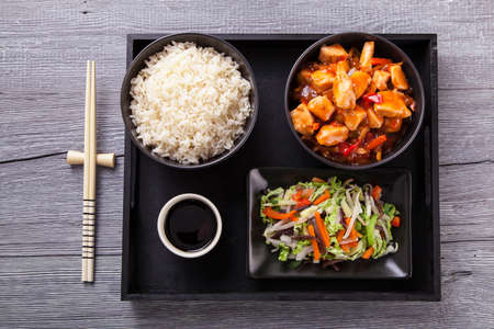 Chinese chicken sweet and sour sauce, served with rice and vegetables on woodboard