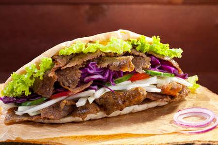 Beef Kebab in a bun on woodboard photo