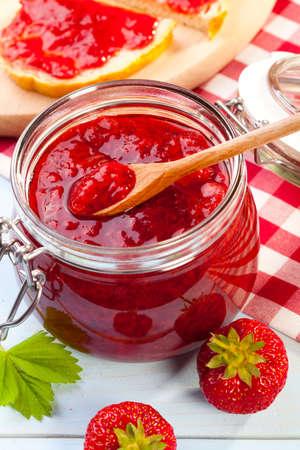 jam jar: Home made strawberry jam on blue woodboard Stock Photo
