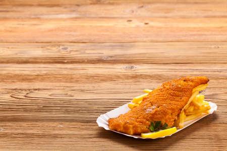 fish and chips: Pescado y patatas fritas en una bandeja de papel - Fondo de madera natural