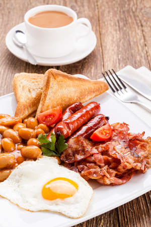 breakfast plate: English breakfast with bacon, sausage, fried egg, baked beans and tea or orange juice