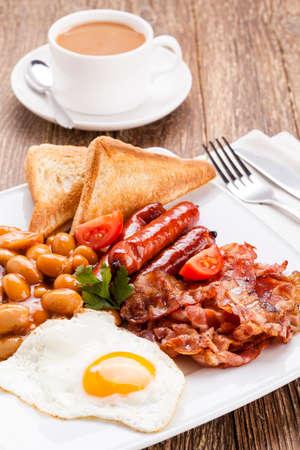 petit dejeuner: Le petit d�jeuner anglais avec du bacon, des saucisses, des ?ufs au plat, f�ves au lard et du th� ou du jus d'orange