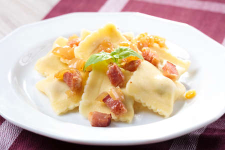 Portion of ravioli with onion and bacon on white plate Archivio Fotografico