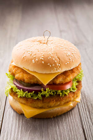 grilled chicken: Home made chicken burger with cheese, lettuce, tomato and onion on wooden board Stock Photo