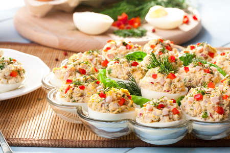 red cooked: stuffed eggs with ham, red pepper and dill on plate Stock Photo