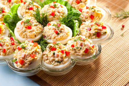 stuffed fish: stuffed eggs with ham, red pepper and dill on plate Stock Photo