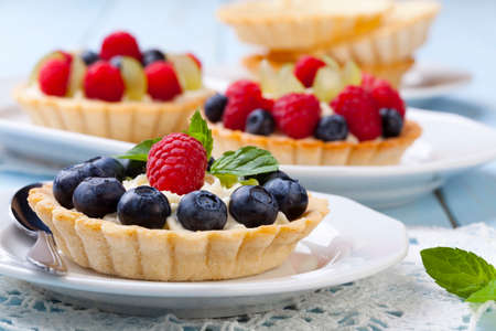 Delicious tartlets with fruit and cream mascaropne on plate Stok Fotoğraf - 42927042