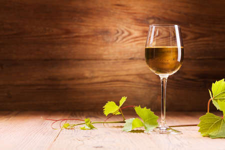 copa de vino: Vaso de vino blanco sobre un fondo de madera Foto de archivo