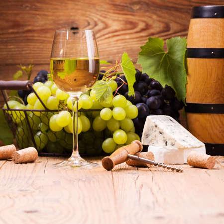화이트 와인의 유리, 나무 배경에 포도와 치즈와 함께 제공
