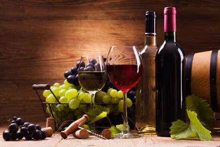 Glazen rode en witte wijn, geserveerd met druiven op een houten achtergrond