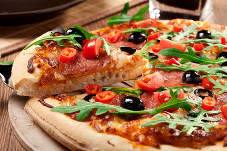Pizza peperoni op plaat met zwarte olijven, rucola en mozzarella kaas Stockfoto