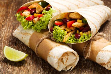 wraps: Burritos envuelve con pollo, frijoles y verduras en la tabla de madera