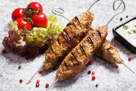 barbecued: Barbecued kofta - kebeb with vegetables on a plate. Selective focus