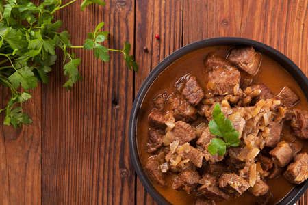 Preparing beef stew - wooden background Foto de archivo