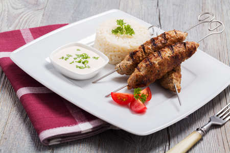 lebanese food: Barbecued kofta - kebeb with rice and vegetables on a plate. Selective focus